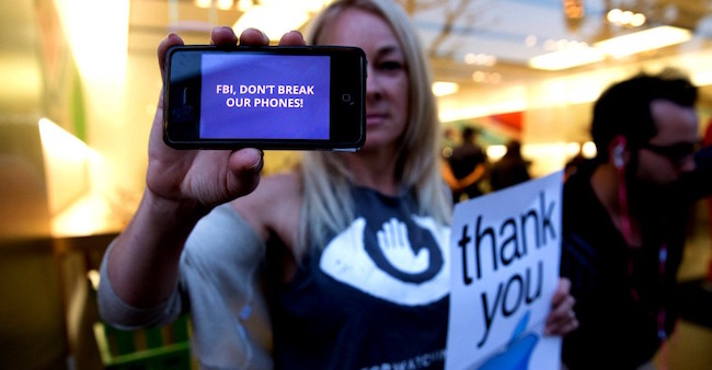 epa05177807 A demonstrator shows a mobile phone with a banner reading 'FBI, DON'T BREAK OUR PHONES!' in front of an Apple Store in San Francisco, California, USA, 23 February 2016. The protest is to show support for Apple Inc., on its refusal to to help the FBI to gain encryption 'backdoor' access to information on the iPhone that belong to one of the two people who killed 14 people in the San Bernadino terror attack. EPA/EUGENE GARCIA (Newscom TagID: epalivetwo037500.jpg) [Photo via Newscom]